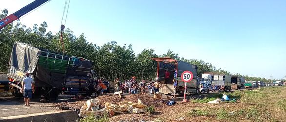 Xe tải chở hạt điều lật, người dân xắn tay áo xúm lại gom giúp tài xế - Ảnh 1.