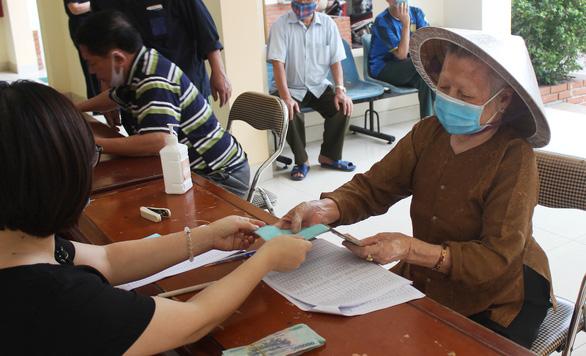 Người dân Hà Nội nhận tiền hỗ trợ ngay ngày lễ - Ảnh 1.