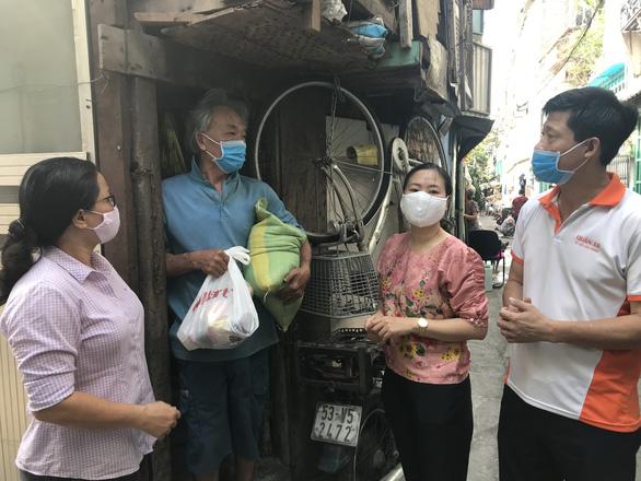 Cán bộ phường nấu cơm, phát gạo cho người nghèo mùa dịch - Ảnh 1.