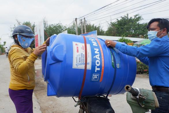 Bà con vùng hạn mặn Long An vui mừng nhận bồn chứa nước - Ảnh 1.