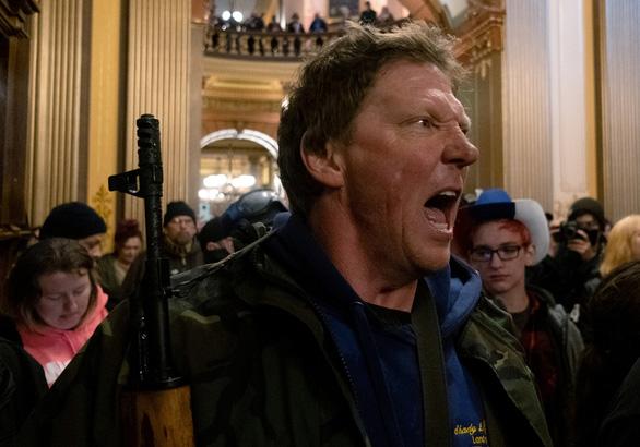Mang súng biểu tình phản đối ở nhà, đòi mở cửa trở lại bang Michigan - Ảnh 1.