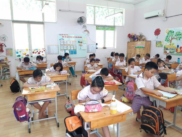 Học sinh tiểu học TP.HCM ngồi so le trong ngày trở lại trường - Ảnh 1.