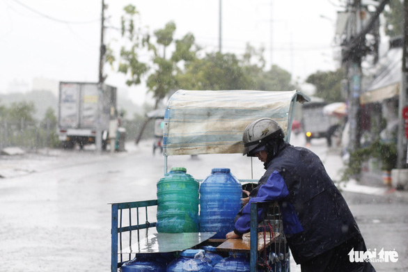 TP.HCM: Mưa lớn nước chảy như lũ trên phố, cây gãy cành đè người đi đường - Ảnh 2.