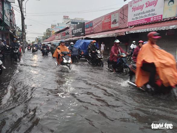 TP.HCM: Mưa lớn nước chảy như lũ trên phố, cây gãy cành đè người đi đường - Ảnh 3.