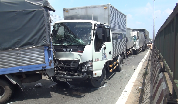 Hơn chục xe tông nhau trên quốc lộ 1, phụ xe tải mắc kẹt trong cabin - Ảnh 3.