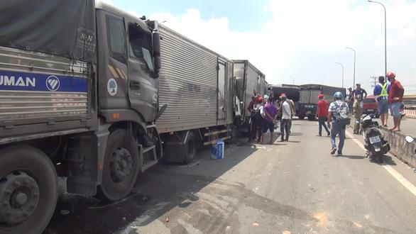 Hơn chục xe tông nhau trên quốc lộ 1, phụ xe tải mắc kẹt trong cabin - Ảnh 1.