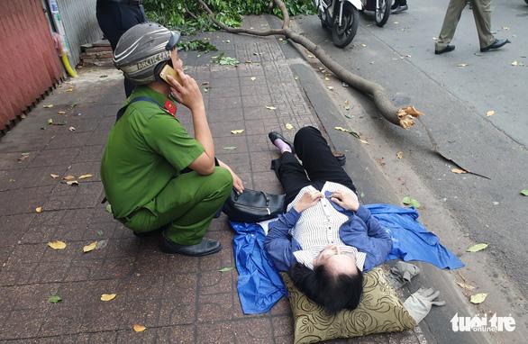 Cành cây to 'trên trời rơi xuống làm người phụ nữ đi xe máy bị thương - Ảnh 2.