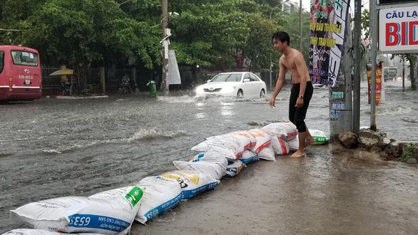 Mưa như trút nước, người dân lấy bao cát chắn nước tràn vào nhà - Ảnh 1.