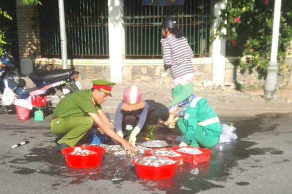 Dễ thương anh công an, chị lao công giúp dân lượm hết mớ cá đổ trên đường - Ảnh 1.