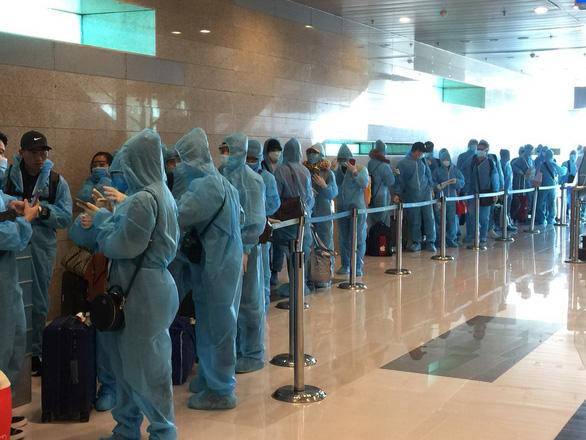 Hơn 240 người Việt từ Singapore đã về đến Tân Sơn Nhất - Ảnh 1.