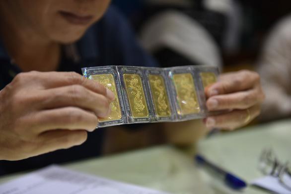 Vàng thế giới bốc hơi gần 17 USD/ounce, trong nước chỉ giảm 100.000 đồng/lượng - Ảnh 1.