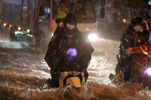TP.HCM mưa liên tục nhiều giờ, dân bì bõm lội nước trên hàng loạt tuyến đường - Ảnh 1.