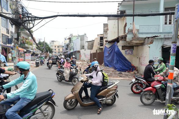 Các hộ dân tháo dỡ nhà, mở rộng nút cổ chai đường Bùi Đình Túy - Ảnh 1.