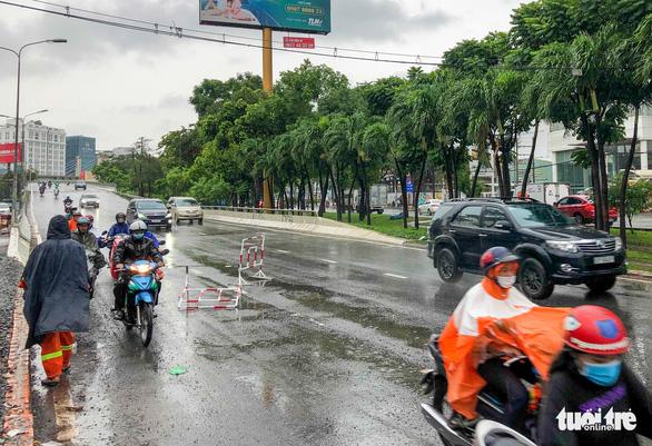 Đổ dốc cầu vượt gặp ngay hố lún, nhiều người đi xe máy té ngã - Ảnh 2.