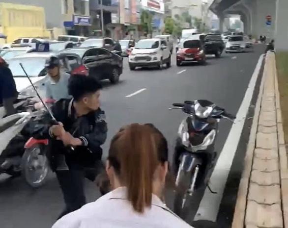 Sau va chạm với bà bầu, nam thanh niên cầm gậy dọa đánh người đi đường, vụt nát đầu xe máy - Ảnh 1.