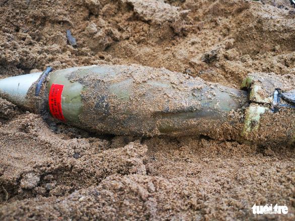 Phát hiện trái đạn cối trong bãi cát cửa hàng vật liệu xây dựng - Ảnh 1.