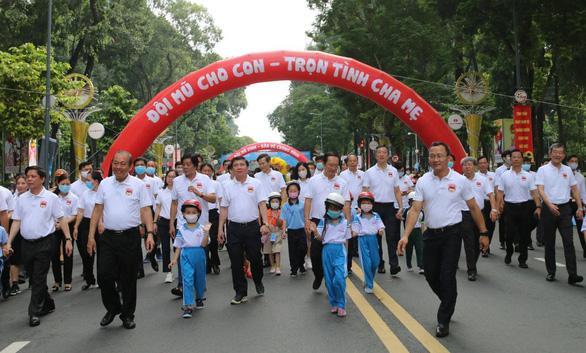 Phó thủ tướng Trương Hòa Bình đi bộ vận động đội mũ bảo hiểm cho trẻ em - Ảnh 1.
