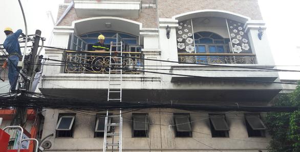 Cháy công ty in vải ở Tân Bình, nhân viên đu dây xuống, 2 người mắc kẹt - Ảnh 2.