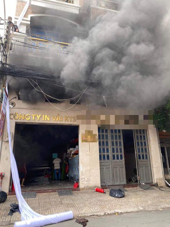 Cháy công ty in vải ở Tân Bình, nhân viên đu dây xuống, 2 người mắc kẹt - Ảnh 1.