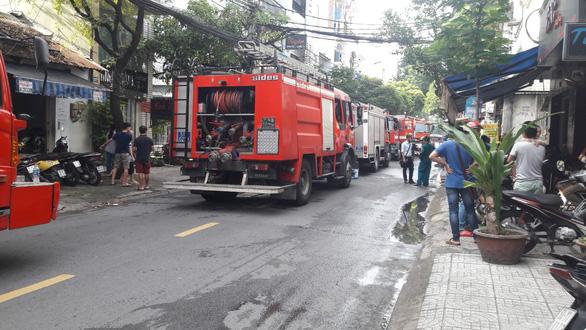 Cháy công ty in vải ở Tân Bình, nhân viên đu dây xuống, 2 người mắc kẹt - Ảnh 4.