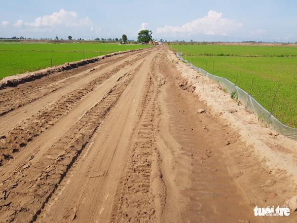 Cho chính quyền mượn đất mở đường giữa đồng lúa giúp dân vùng sạt lở đi lại - Ảnh 1.