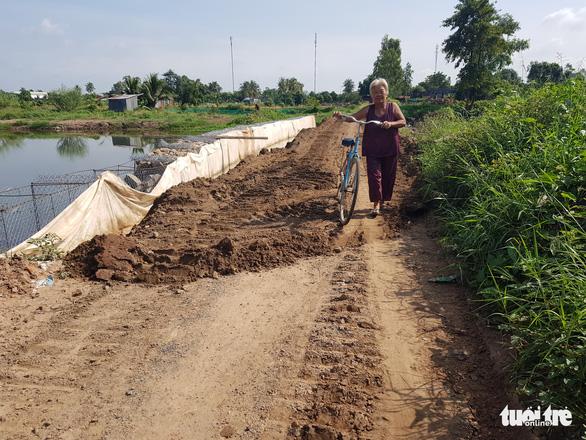 Cho chính quyền mượn đất mở đường giữa đồng lúa giúp dân vùng sạt lở đi lại - Ảnh 2.
