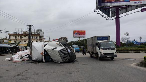 Xe container ôm cua lật ngang giữa bùng binh, tài xế thoát chết - Ảnh 1.