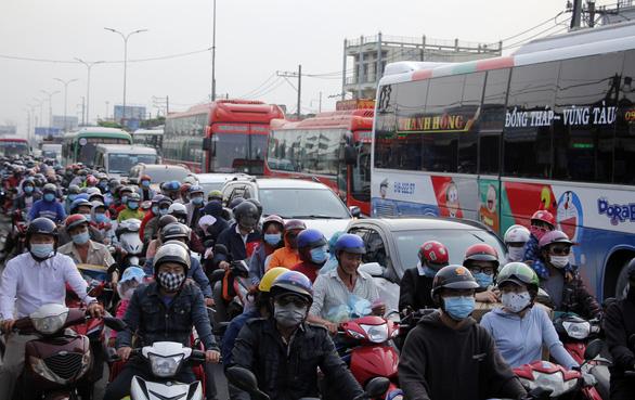 Từ 16h chiều 3-1, cửa ngõ miền Tây của Sài Gòn đông dần, trái cây, gà qué đu xe - Ảnh 1.