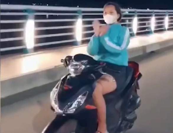 Phạt cô gái múa quạt, thả tim khi chạy xe máy trên cầu Thạch Bích - Ảnh 1.