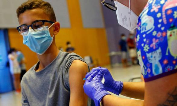 Cậu bé 14 tuổi được tiêm vắc xin COVID-19 của Moderna ở Tây Ban Nha - Ảnh: REUTERS