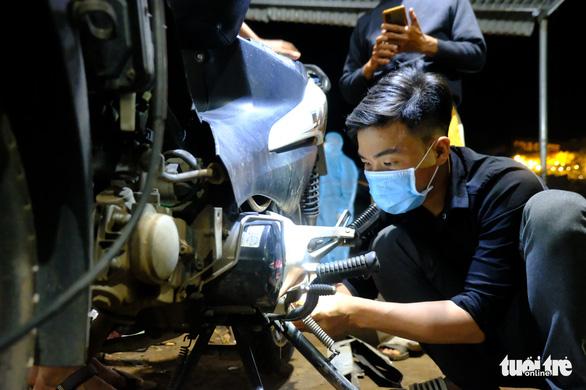 Đội SOS trắng đêm sửa xe miễn phí cho người về quê - Ảnh 1.