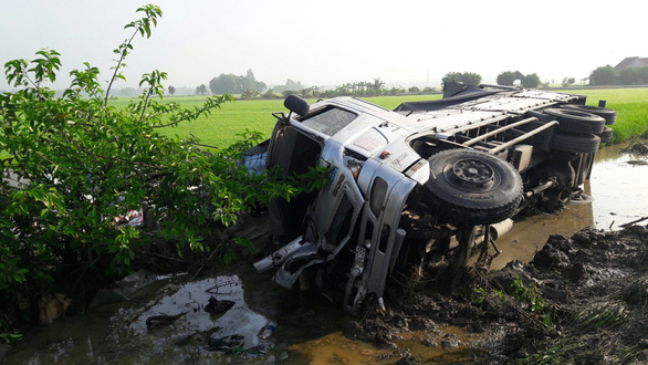 Xe khách đi lễ chùa tông với xe tải cùng văng xuống ruộng, 1 người chết - Ảnh 1.