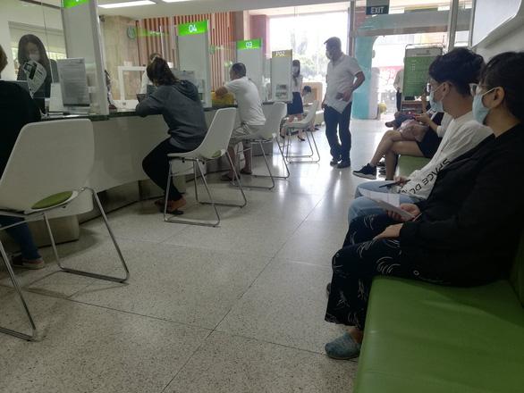 Ngày làm việc cuối của ngân hàng trước kỳ nghỉ tết: phòng giao dịch khá đông, ATM bớt kẹt - Ảnh 1.