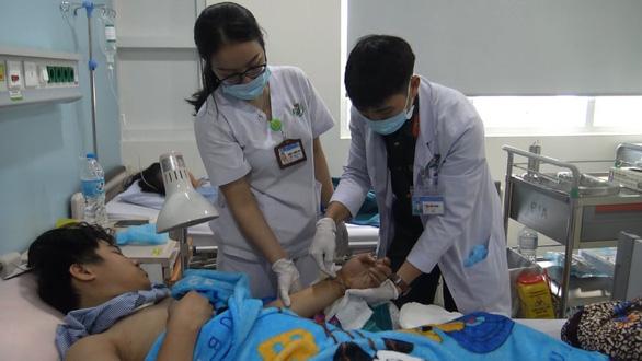 Bệnh viện 175 'cứu sống' hai bàn tay gần đứt lìa của hai thanh niên - Ảnh 1.