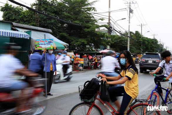 Bà ngoại Hai cầm bảng canh xe cho học trò qua đường an toàn - Ảnh 1.