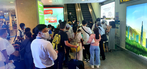 Sân bay Tân Sơn Nhất đông nghẹt, khách xếp hàng suýt lỡ chuyến - Ảnh 4.