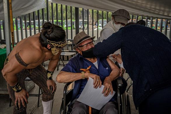 Mexico mời đô vật trấn an người già đi tiêm vắc xin COVID-19 - Ảnh 1.