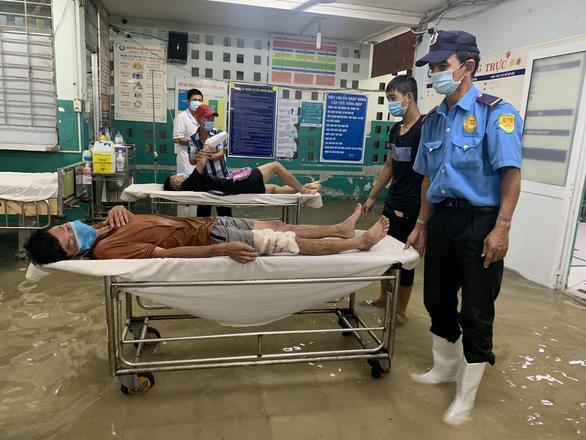 Mưa 3 tiếng, bác sĩ bệnh viện ở Hóc Môn xắn quần lội nước khám bệnh - Ảnh 3.