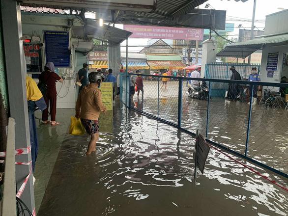 Mưa 3 tiếng, bác sĩ bệnh viện ở Hóc Môn xắn quần lội nước khám bệnh - Ảnh 5.