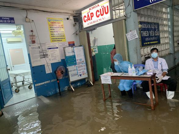 Mưa 3 tiếng, bác sĩ bệnh viện ở Hóc Môn xắn quần lội nước khám bệnh - Ảnh 2.