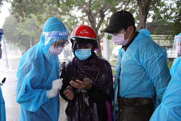 Tình nguyện viên dầm mưa dãi nắng trực chốt chống dịch COVID-19 - Ảnh 2.