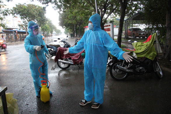 Tình nguyện viên dầm mưa dãi nắng trực chốt chống dịch COVID-19 - Ảnh 1.