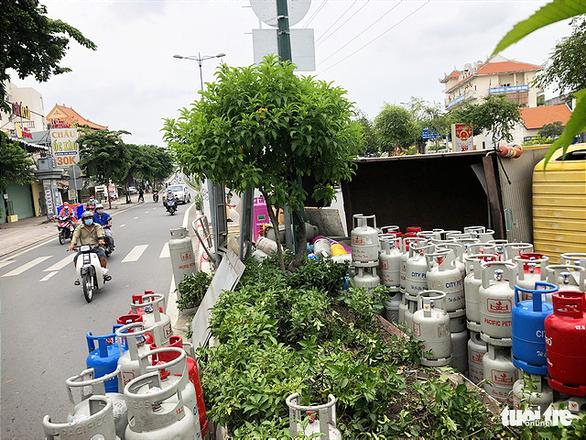 Lật xe chở gas, hàng chục bình gas văng xuống đường Phạm Văn Đồng - Ảnh 2.