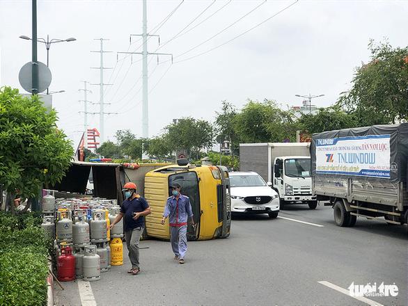 Lật xe chở gas, hàng chục bình gas văng xuống đường Phạm Văn Đồng - Ảnh 3.