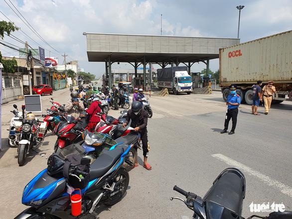 Người khai báo y tế ở chốt cầu Đồng Nai xong được gửi về địa phương liên hệ cách ly - Ảnh 3.