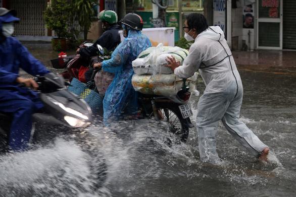 TP.HCM mưa trắng trời, nhân viên trực chốt đẩy xe dân qua chỗ ngập - Ảnh 1.