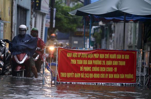 TP.HCM mưa trắng trời, nhân viên trực chốt đẩy xe dân qua chỗ ngập - Ảnh 2.