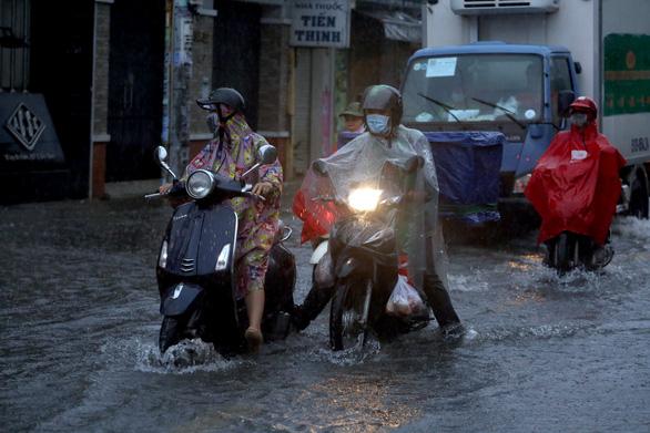 TP.HCM mưa trắng trời, nhân viên trực chốt đẩy xe dân qua chỗ ngập - Ảnh 3.