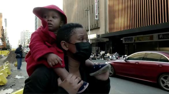 Video người mẹ trên tòa nhà cháy thả con xuống nhờ đám đông bên dưới chụp lấy cứu sống - Ảnh 2.