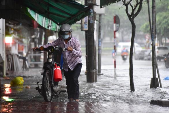 TP.HCM mưa trắng trời, nhân viên trực chốt đẩy xe dân qua chỗ ngập - Ảnh 4.
